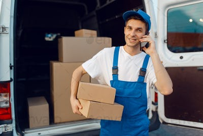 Deliveryman in uniform holds parcel and phone