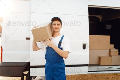 Deliveryman in uniform holds carton box at the car