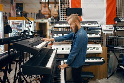 Young man choosing synthesizer in music store