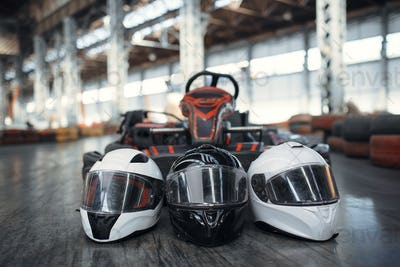 Go kart car and helmets on the ground, karting