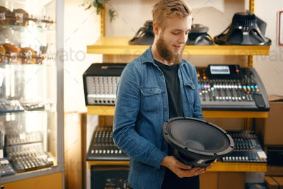 Musician buying subwoofer speaker in music store
