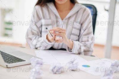 Crop businesswoman crumpling paper while writing