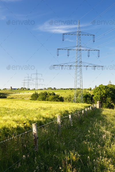Electricity Pylons In Green Landscape