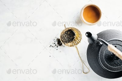 Teapot with tea on bright background
