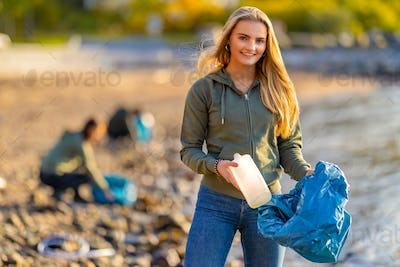 Volunteer holding bottle and garbage bag at beach