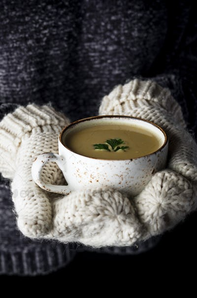 Girl in mittens holding a cup of soup