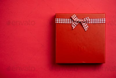 Flat lay a single red Christmas gift on red