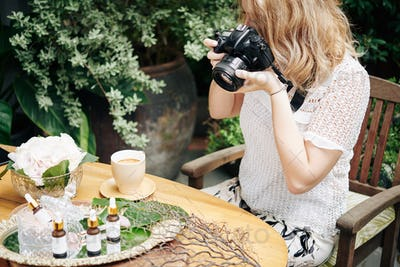 Woman photographing organic cosmetics