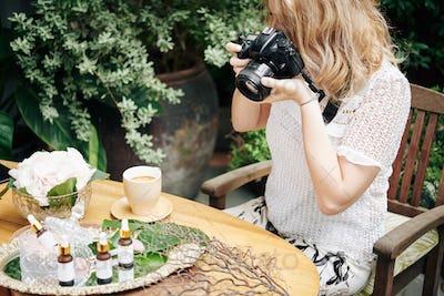 Woman photographing organic cosmetics
