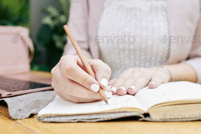 Businesswoman writing down thoughts