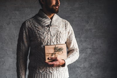 A man holds a craft box for a Christmas present in a beige sweater on a gray background