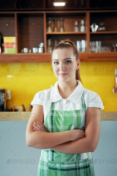 Young woman in apron working in coffee shop