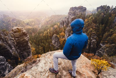 Hiker in outdoor clothing enjoying the sunset on mountain top with beautiful view of cliffs ridge