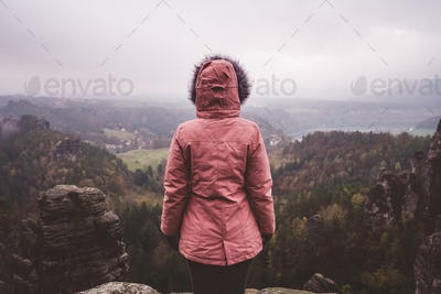 Young woman in outdoor clothing standing alone on mountain top with wild forest in the valley in