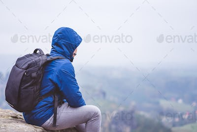 Lonely hiker wear outdoor clothing with backpack sitting on mountain edge, enjoying view of