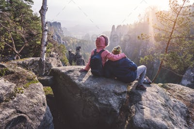 Young couple in outdoor clothing with backpacks resting after hike on limestone rock enjoying back
