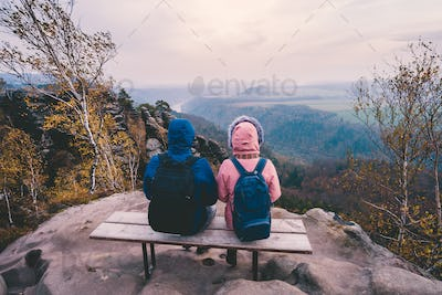 Young couple in outdoor clothing with backpacks sitting and rest on bench enjoying view of mountain
