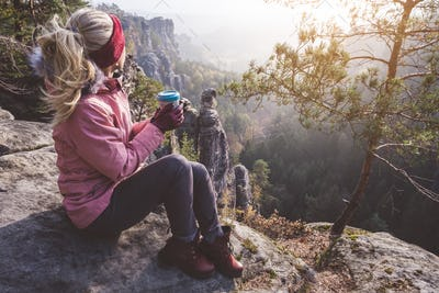 Female blond hiker outdoor clothing with coffee cup in hands on limestone rock enjoying sunset back