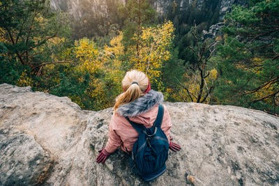 Young woman in outdoor clothing with backpack sitting on cliff's edge enjoying view of autumnal