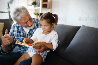 Cute little girl playing with her grandfather at home. Happy family concept