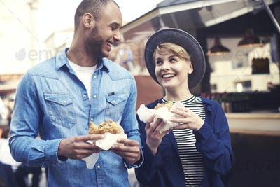 Cheerful couple trying the best hamburgers in the city