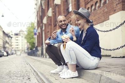 Couple having fast food sitting on the sidewalk