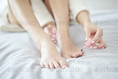 Low section of woman doing pedicure