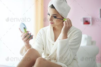 Young woman doing her make up at the morning