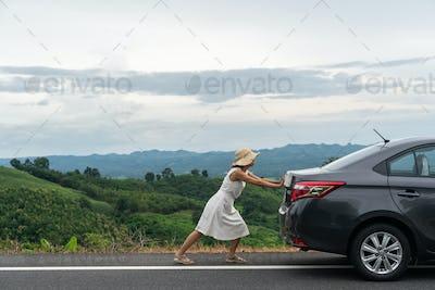 Young woman traveler pushing a broken car down the road