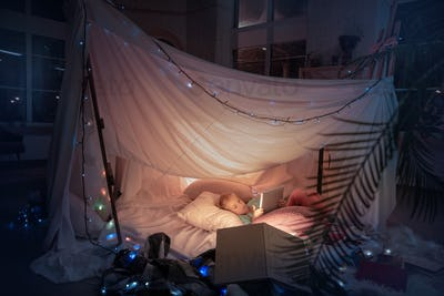 Little girl lying in a teepee, playing with the flashlight