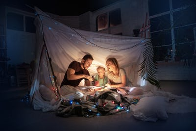 Family sitting in a teepee, reading stories with the flashlight