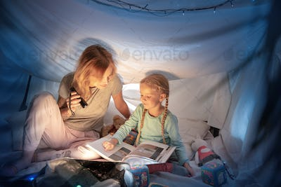 Mother and daughter sitting in a teepee, reading stories with the flashlight