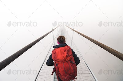 Female tourist walking across a suspension bridge in heavy fog