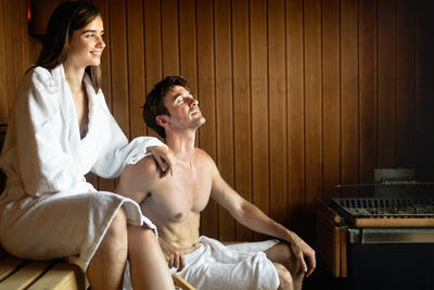 Beautiful young couple sitting together in a sauna