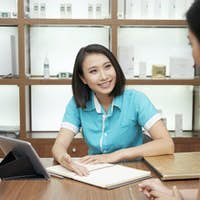 Smiling receptionist and client in spa salon