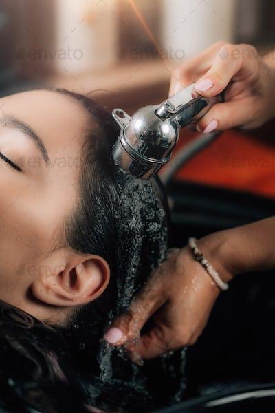 Hairdresser Rinsing Woman's Hair.