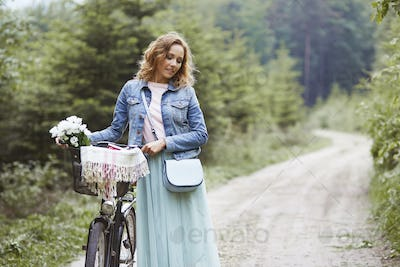 Walking woman with bike in the forest