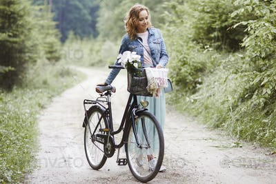 Woman with bike walking in forest