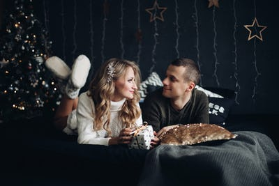 Couple on bed with Christmas present. New Year