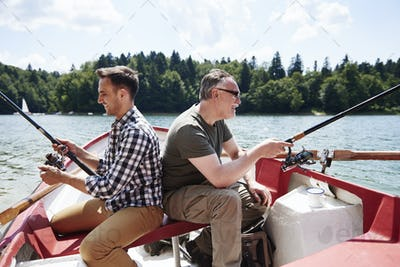 Son and father with fishing rod on a boat