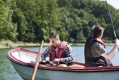Son and father in boat make preparations for fish