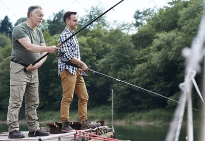 Serious male friends fishing together