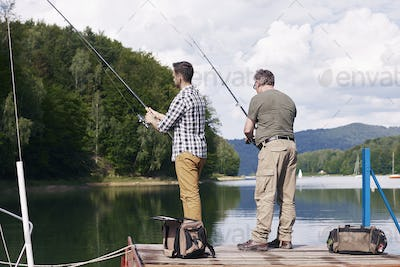 Rear view of son and father fishing