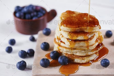 Pancakes with honey and blueberry on cutting board