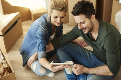 Couple around cardboard boxes with digital tablet
