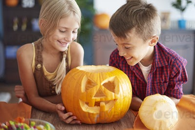Cheerful children and carved pumpkin