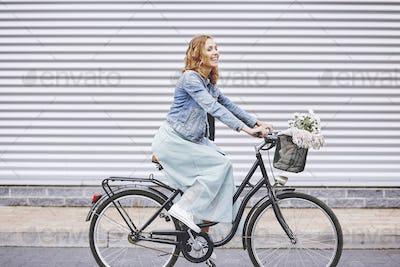 Happy adult woman enjoying the cycling