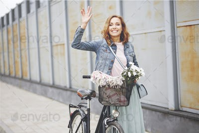 Beauty woman with bike waving for someone