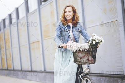 Adult woman with bike in the city