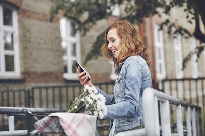Woman with modern mobile phone in the city
